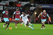 Bafetimbi Gomis of Swansea city © breaks away from James Collins of West Ham (r). Barclays Premier league match, Swansea city v West Ham Utd at the Liberty Stadium in Swansea, South Wales  on Sunday 20th December 2015.<br /> pic by  Andrew Orchard, Andrew Orchard sports photography.