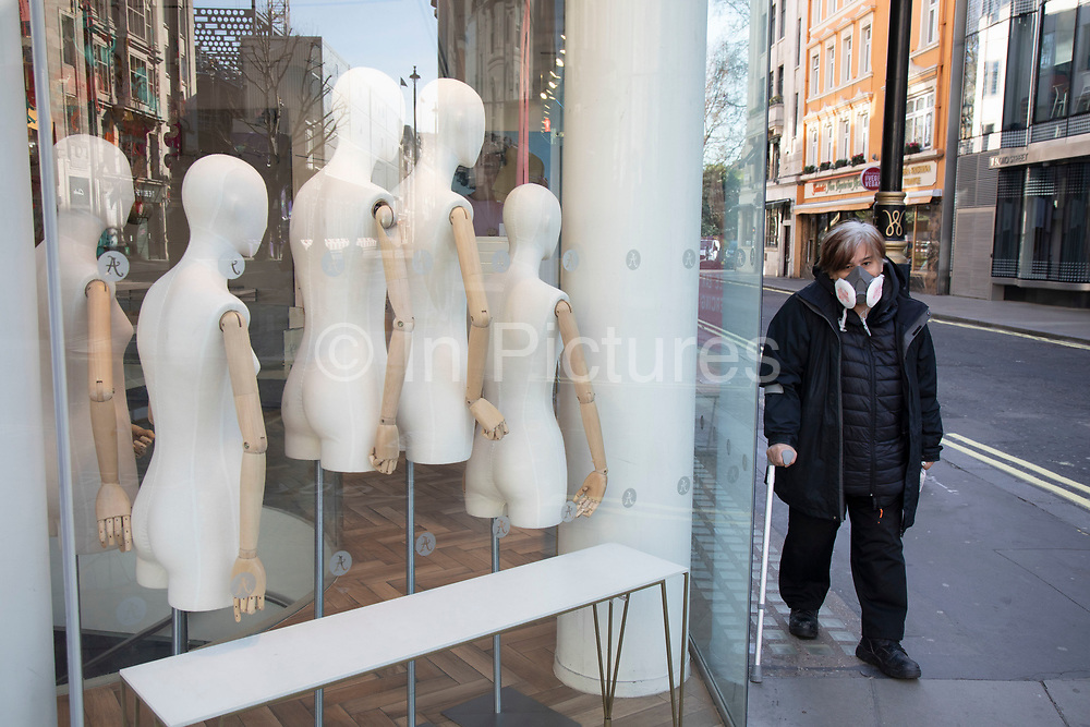 Figure wearing a face mask walks past blank mannequins on Oxford Street, Londons main shopping and retail area normally full of thousands of shoppers and traffic is virtually deserted due to the Coronavirus outbreak on 23rd March 2020 in London, England, United Kingdom. Following government advice most shoppers are staying at home leaving the streets quiet, empty and eerie. Coronavirus or Covid-19 is a new respiratory illness that has not previously been seen in humans. While much or Europe has been placed into lockdown, the UK government has announced more stringent rules as part of their long term strategy, and in particular social distancing.