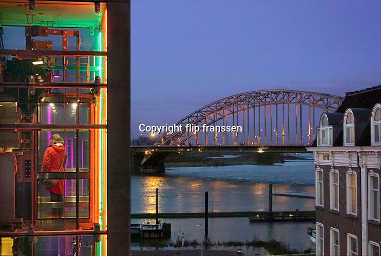 Nederland, Nijmegen, 21-12-2019 Zicht op de Waalbrug vanag het groene balkon . Hier is een lift naar de waalkade . De oude waalbrug is gebouwd in 1936 en was destijds de langste boogbrug van europa . gebouwd van plaatstaal, staal . De donkere dagen voor kerst . Foto: Flip Franssen