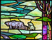 Stained glass window church of Saint Mary, Martlesham, Suffolk, England, UK by Walter J Pearce in Arts and Craft style, 1903 Return of the Prodigal Son brother working ploughing in field