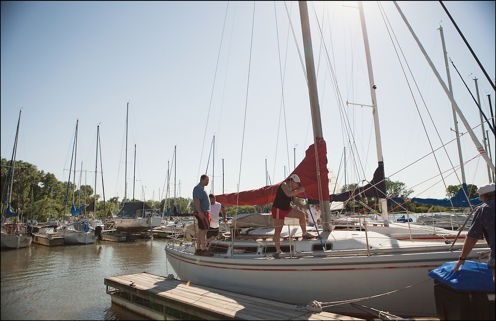 Friends prepare a sailboat for a regatta at Cheney Lake in Kansas.