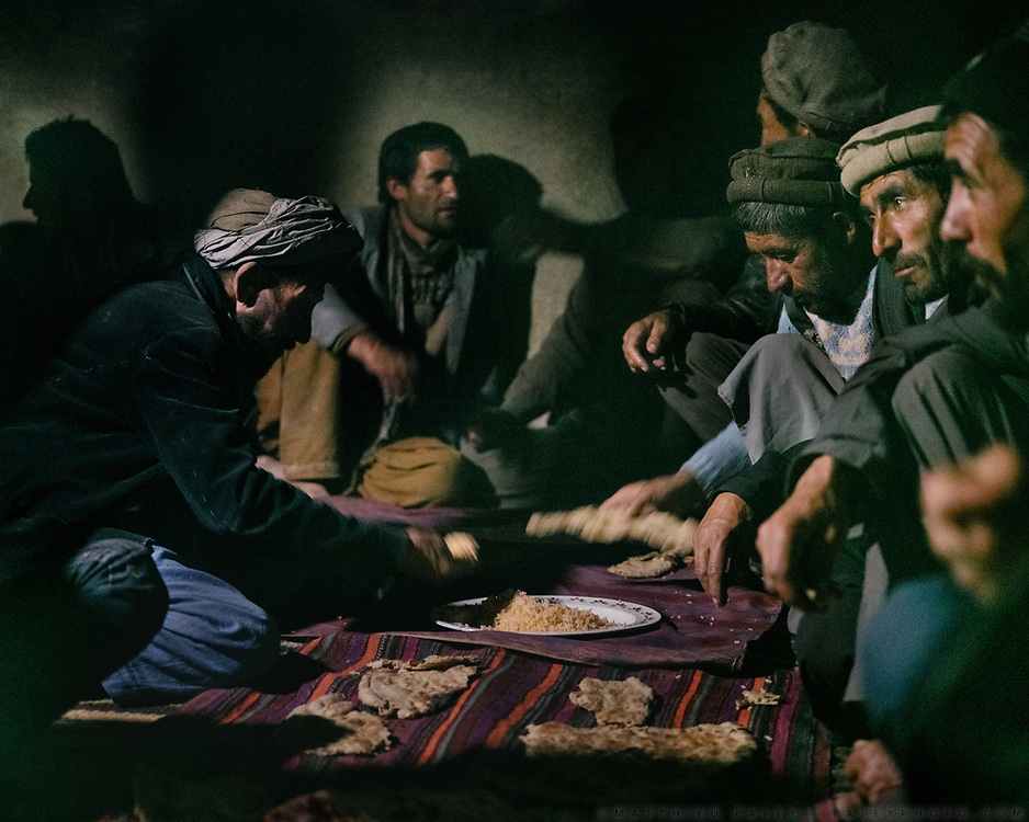 Men huddled in a house during a wake, following a funeral.  The traditional life of the Wakhi people, in the Wakhan corridor, amongst the Pamir mountains.