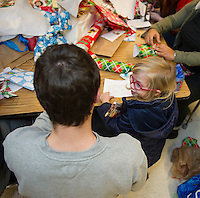 Kyle Johnson helps Lillyana Lyons wrap presents for her family during Pleasant Street School's Mall Shop on Friday evening.  (Karen Bobotas/for the Laconia Daily Sun)
