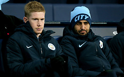 Manchester City's Kevin De Bruyne (left) and Riyad Mahrez (right) in the dugout during the Premier League match at the Etihad Stadium, Manchester.