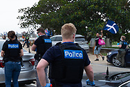 Undercover police officers watch on as demonstrators march along St. Kilda Beach during the Sack Daniel Andrews Protest in Fawkner Park. Parts of the community are looking to hold the Victorian Premier accountable for the failings of his government that led to more than 800 deaths during the Coronavirus crisis. Victoria has recorded 36 days Covid free as pressure mounts on the Premier Daniel Andrews to relax all remaining restrictions. (Photo by Mikko Robles/Speed Media)