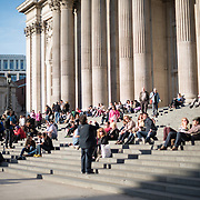 People sittingon the steps of St Paul's Cathedral, one of the most distinctive of London's landmarks. There has been a church on this site since 604 AD. The current building, with it's massive dome, was designed by Christopher Wren and dates back to the late 17th century.