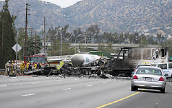 April 25, 2017 - Los Angeles, California, U.S - Firefighters and police officers inspect the scene after a multi-vehicle crash involving two big rigs and multiple passenger vehicles, on 5 Freeway near Griffith Park, Tuesday, April. 25, 2017, in Los Angeles. The crash left one person dead and nine others injured, one critically and forced the closure of the Golden State (5) Freeway in both directions in the Los Feliz area. (Credit Image: © Ringo Chiu via ZUMA Wire)