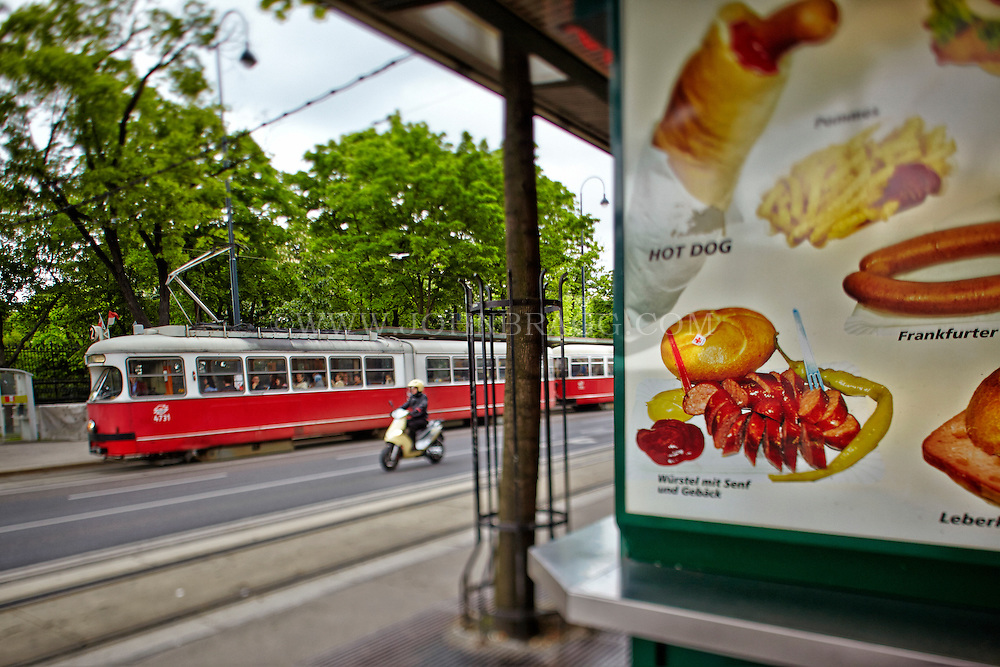 View of a food billboard, scooter, and a red and white tram, Vienna, Austria.
