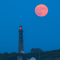 Massachusetts photography of full moon and South Tower Lighthouse at moonrise. This beautiful Massachusetts lighthouse is located on Cape Ann, Massachusetts.<br />