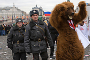 Moscow, Russia, 06/12/2007..To Russian policemen and a Putin supporter in a bear costume, as approximately 30,000 members of the pro Kremlin youth organisation Nashi [Ours], demonstrate outside the Kremlin in support of President Vladimir Putin, and celebrate the victory of his United Russia party in the recent parliamentary elections.