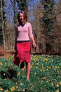 A912R5 Young girl walking in daffodil woods