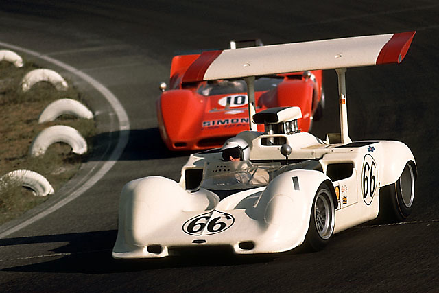 Jim Hall in his Chaparral 2G leads Chuck Parsons' Lola T162 through the mildly banked, original Turn 9 at Riverside.