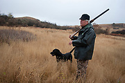Experienced hunter Byron Grubb with his black labrador retriever Danny out on the North Dakota prarie grasslands, shooting upland game birds such as grouse near Minot, North Dakota, United States. Byron has been shooting for most of his life and puts considerable efforts into his hunting, efforts which reward him with wild game meats, none of which is wasted. This cold wet morning is not ideal for this type of shooting as the birds tend to sit tight in the undergrowth. The hunters on occasion nearly tread on the birds before they will take flight.