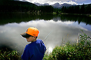"""Eight year-old Alexander Moody of Springfield, Ill. fishes for trout in Sprague Lake at Rocky Mountain National Park on Thursday August 18, 2005. Moody was vacationing with family at the park and his mom, Conny, said, """"this is a great park for families"""". The park, open since 1915, is a showcase of the grandeur of the Rocky Mountains and features peaks ranging from 8,000 to 14,259 feet tall and is home to elk, mule deer, bighorn sheep, black bears, coyotes and a wide range of birds, fish and smaller animals.  Rocky Mountain National Park is located in the north-central region of the U.S. state of Colorado..Rocky Mountain National Park features majestic mountain views, a variety of wildlife, varied climates and environments?from wooded forests to mountain tundra?and easy access to back-country trails and campsites. The park is located north-west of Boulder, Colorado in the Colorado Rockies, and includes the Continental Divide and the headwaters of the Colorado River in its land area.Rocky Mountain National Park encompasses approximately 265,770 acres (1,076 km²) of land in Colorado's northern Front Range. The park is split by the Continental Divide, which gives the eastern and western portions of the park a different character. The east side of the park tends to be dryer, with heavily glaciated peaks and cirques. The west side of the park is wetter and more lush, with deep forests dominating..The park contains 359 miles (578 km) of trails, 150 lakes, and 450 miles (720 km) of streams. The park contains over 60 named peaks higher than 12,000 feet (3,700 m), and over one fourth of the park resides above tree line. The highest point of the park is Longs Peak, which rises to 14,259 feet above sea level. Longs Peak is the only fourteen thousand foot peak in the park..(MARC PISCOTTY/ © 2005)"""