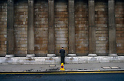 Beneath the giant, solid pillars of the Bank of England in the heart of London's financial district – the ancient Square Mile – a man dressed in a traditional pinstripe suit has stopped to make a phone call or check for messages. Halting his journey along this street he has opted to stand in line with a traffic no waiting cone and also near double-yellow lines that restrict parking or stopping. Without the cone or lines this scene would otherwise be without colour - the columns of this financial institution and the pavement (sidewalk) are drab – so the welcome yellow gives this picture more interest. We only see the man from the rear view and so he remains anonymous, a small person set against the scale of a large-scale financial landscape.