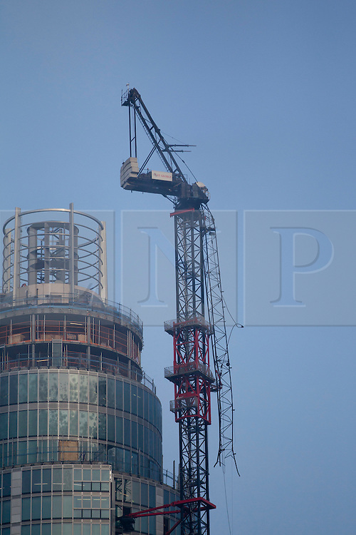 © Licensed to London News Pictures. 16/01/2013. London, UK. A damaged crane is seen hanging from the side of the St George's Wharf development near Vauxhall in in London today (16/01/13) after a being hit by a helicopter, which then crashed. Photo credit: Matt Cetti-Roberts/LNP