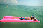 Boy on pink raft, Gulf of Mexico, Florida
