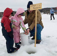 5 year old Kara Stephens along with her brother Hunter and dad Brian releases her fish back into Lily Pond during the Ice Fishing Derby held Sunday morning.  (Karen Bobotas/for the Laconia Daily Sun)