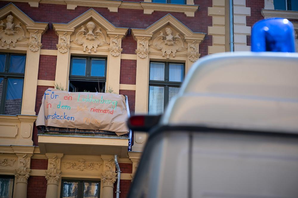 """Solidaritätskundgebung gegen rechte Gewalt im Weitlingkiez in Berlin Lichtenberg. Nach einem fremdenfeindlichen Angriff mit einem Kampfhund auf die Inhaberin eines Eiscafes und ihren Begleiter in der Margaretenstrasse protestieren ca. 60 Menschen ihre Solidarität und demonstrieren gegen Rassismus und Fremdenfeindlichkeit. Banner """"Für ein Lichtenberg in dem sich niemand verstecken muss"""" an einem Balkon.<br /> <br /> [© Christian Mang - Veroeffentlichung nur gg. Honorar (zzgl. MwSt.), Urhebervermerk und Beleg. Nur für redaktionelle Nutzung - Publication only with licence fee payment, copyright notice and voucher copy. For editorial use only - No model release. No property release. Kontakt: mail@christianmang.com.]"""