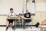 Will Beckwith, 15, a ninth-grader at Noe Middle School, center, acts as scorekeeper as Tournament Director Jason Thompson moderates at the beginning of the round four match between teams Edmonson, left, and Meyzeek B.<br /> <br /> Teams compete in the preliminary rounds of the 2019 Kentucky Quiz Bowl Alliance Middle School State championship Saturday, April 27, 2019, at Noe Middle School in Louisville, Ky. (Photo by Brian Bohannon)