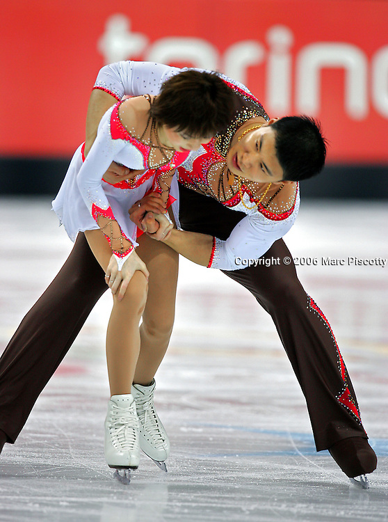 Chinese skater Dan Zhang (left) grasps for her knee as skating partner Hao Zhang (right) checks to see if she's hurt after a hard fall on a throw during the free skate portion of the Pairs Figure Skating event at the Palavela ice arena in Turin, Italy Monday February 13, 2006. The Russian figure skaters Tatiana Totmianina and Maxim Marinin won the gold medal with a total score of 204.48 while Chinese skaters Dan Zhang and Hao Zhang won the silver medal in dramatic fashion after a hard fall by Dan caused a couple minute break in their program after she hurt her knee on the fall..(Photo by Marc Piscotty / © 2006)