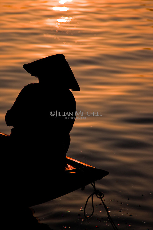 Woman wearing conical hat silhouette on the Thu Bon river in Hoi An at sunrise.