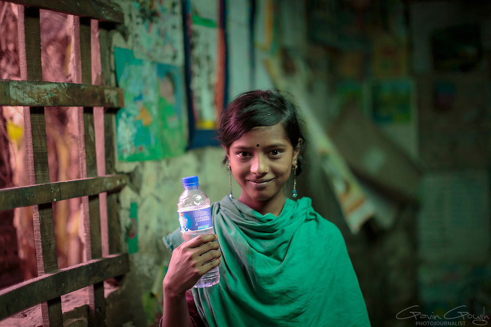 A schoolgirl standing in a classroom, holding a bottle containing clean water