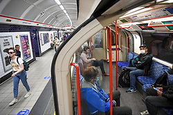 © Licensed to London News Pictures. 23/04/2020. London, UK. Commuters during evening rush hour do their best to observe social spacing on a Central Line train. Transport for London are furloughing a third of their staff as demand for the network falls drastically during the Coronavirus lockdown.  Photo credit: Guilhem Baker/LNP