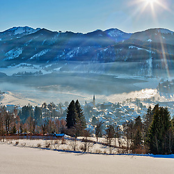 Snow covered town and mountain during sunrise