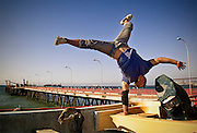 A breakdancer jumping on a boat with a dock as background