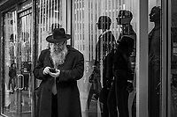A Jewish man checks his phone under the watchful eyes of  silent guards.