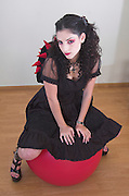 A model wearing Gothic style clothes with a ball and a bag