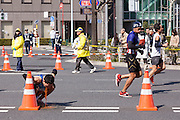 Arunner vomits in the streets of Asakusa during the 10th Tokyo Marathon took place on a fine spring day in Tokyo Japan. Sunday February 28th 2016. Thirty-six thousand runners took part with Ethiopian,  Feyisa Lilesa winning the  men's competition and  Kenyan, Helah Kiprop victorious in the women's race.