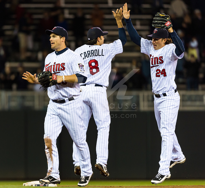 Minnesota Twins Jamey Carroll and Trevor Plouffe, behind Josh Willinghim, celebrate the team's victory against the Los Angeles Angels on May 8, 2012 at Target Field in Minneapolis, Minnesota.  The Twins defeated the Angels 5 to 0. © 2012 Ben Krause