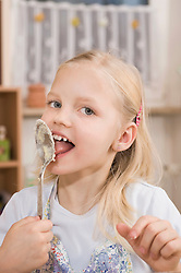 Girl nibbling dough from spoon, portrait