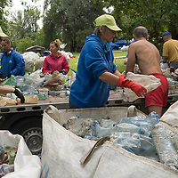 Volunteers of the PET Cup plastic waste recovery challenge work on processing trash they collected from river Tisza in Dombrad, Hungary on Aug. 5, 2020. ATTILA VOLGYI