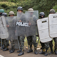Army with riot police equipment and improvised metal batons prepare to confront protestors in Olancho.
