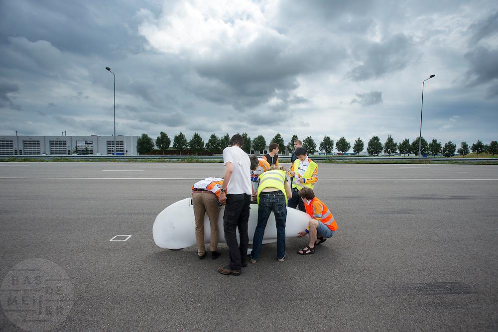Het team verzamelt zich rond de VeloX2 nadat Jan Bos enkele ronden heeft gereden. Het Human Power Team Delft en Amsterdam (HPT) traint op de RDW baan in Lelystad met de VeloX2 voor de recordpoging in september. Het HPT hoopt dan in Amerika meer dan 133 km/h te rijden over 200 meter.<br /> <br /> The team gather around the VeloX2 after Jan Bos finished the test runs. Human Powered Team Delft and Amsterdam (HPT) is training at the RDW test track in Lelystad with the VeloX2 for the record attempt in september.