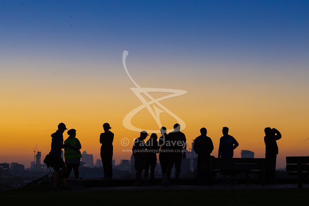 London, October 27 2017. People enjoy the view of The City as the day breaks over London's skyline, seen from Primrose Hill. © Paul Davey