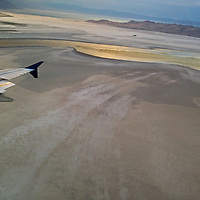 A jetliner prepares to land at Salt Lake City International Airport as a sunset illuminates a tributary to Great Salt Lake.