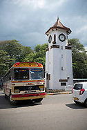 A bus departing the Sri Lankan city of Kandy drives past the Kandy Clock Tower, built in 1950.