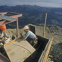 Construction workers assemble a tram station atop 11,166-foot Lone Mountain at Montana's Big Sky Ski Area, a difficult and dangerous project.
