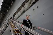 A sailor walks down the gangplank beneath the giant hull of their ship during a tour by the general public on-board the Royal Navy's aircraft carrier HMS Illustrious during a public open-day in Greenwich. Illustrious docked on the river Thames, allowing the tax-paying public to tour its decks before its forthcoming decommisioning. Navy personnel helped with the PR event over the May weekend, historically the home of Britain's naval fleet.