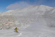 A skier heads down Little Nell run on Aspen Mountain as mist from a snow gun makes a faint rainbow.