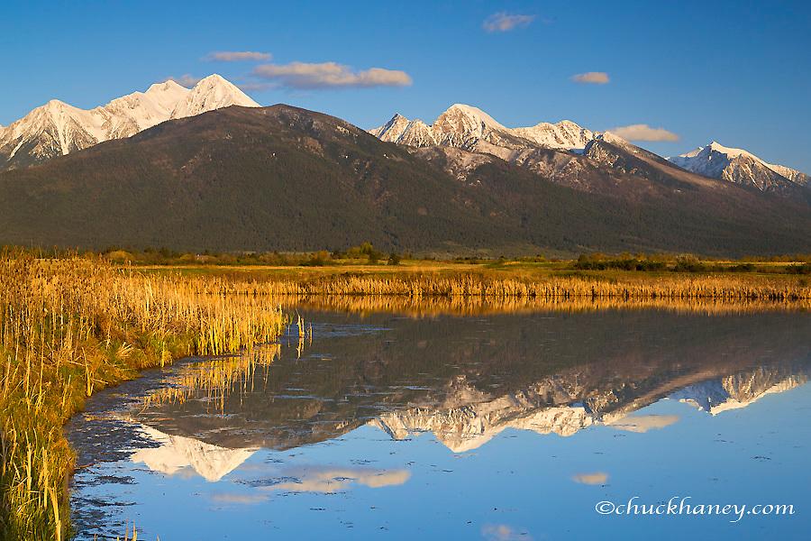 Wetlands pond reflects Mission Mountain Range at Ninepipe WMA near Ronan, Montana, USA