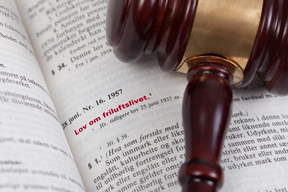Fokus på innledningen til «lov om friluftslivet» i Norges lover. En dommerhammer understreker tematikken. Tittelen er uthevet i rødt.