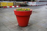 Giant red plant pot containing Marigolds in London, England, United Kingdom.