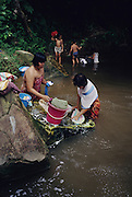 DAYAK WASHING, MALAYSIA. Sarawak, Borneo, South East Asia. Dayak, 'Kelabit', washing clothes in  river. Tropical rainforest and one of the world's richest, oldest eco-systems, flora and fauna, under threat from development, logging and deforestation. Home to indigenous Dayak native tribal peoples, farming by slash and burn cultivation, fishing and hunting wild boar. Home to the Penan, traditional nomadic hunter-gatherers, of whom only one thousand survive, eating roots, and hunting wild animals with blowpipes. Animists, Christians, they still practice traditional medicine from herbs and plants. Native people have mounted protests and blockades against logging concessions, many have been arrested and imprisoned.