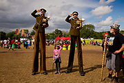 Photo op with soldiers on stilts, Glastonbury Festival.<br /> Glastonbury Festival is the largest greenfield festival in the world, and is now attended by around 175,000 people. It's a five-day music festival that takes place near Pilton, Somerset, England. In addition to contemporary music, the festival hosts dance, comedy, theatre, circus, cabaret, and other arts. It is organised by Michael Eavis on his own land, Worthy Farm in Pilton. Leading pop and rock artists have headlined, alongside thousands of others appearing on smaller stages and performance areas.