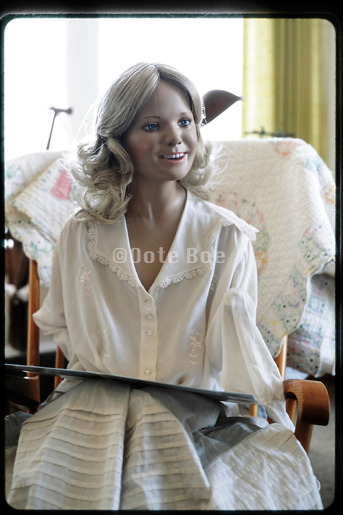 life size female mannequin doll sitting in a homely setting